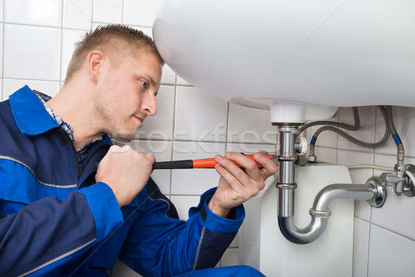 Male Plumber Fixing Sink In Bathroom Stock photo © AndreyPopov