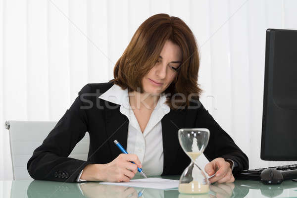 Businesswoman Filling Form In Office Stock photo © AndreyPopov