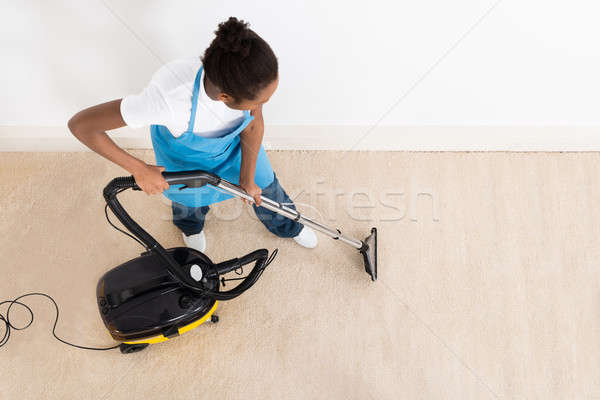 Female Janitor Cleaning Floor With Vacuum Cleaner Stock photo © AndreyPopov