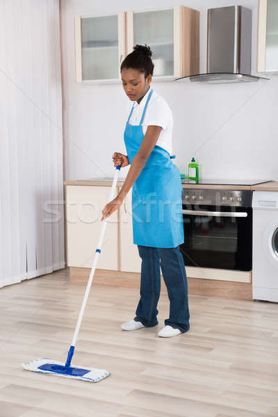 Female Janitor Mopping Floor In Kitchen Stock photo © AndreyPopov