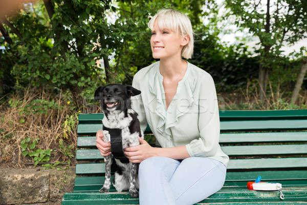 счастливым женщину собака скамейке молодые сидят Сток-фото © AndreyPopov