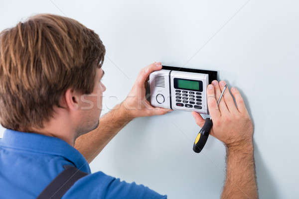 Technician Installing Security System Using Screwdriver Stock photo © AndreyPopov