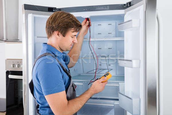 Férfi technikus hűtőszekrény átfogó konyha kábel Stock fotó © AndreyPopov