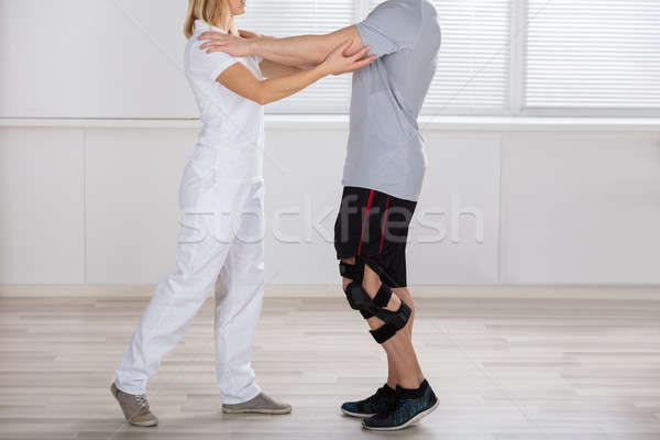Physiotherapist Giving Support To A Male Patient Stock photo © AndreyPopov