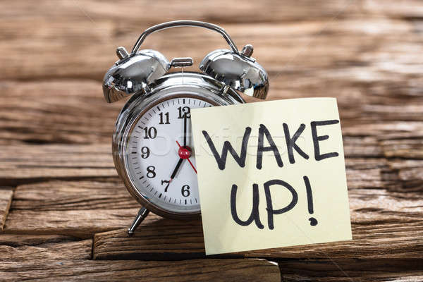 Stock photo: Alarm Clock With Wake Up Text On Sticky Note
