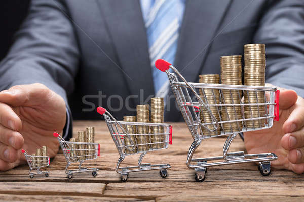 Businessman Covering Coins In Shopping Carts At Table Stock photo © AndreyPopov