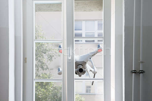 Flying white drone spying through window Stock photo © AndreyPopov