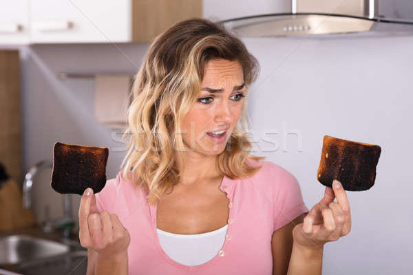Csalódott fiatal nő tart pirítós közelkép konyha Stock fotó © AndreyPopov