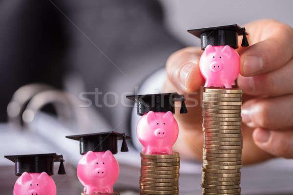 Businessperson Placing Piggybank With Graduation Cap Stock photo © AndreyPopov