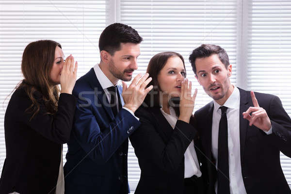 Businesspeople Whispering Into Male Colleague's Ear Stock photo © AndreyPopov