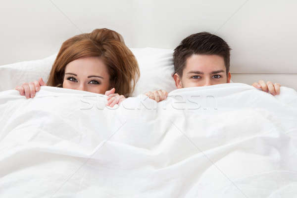Portrait of young couple hiding face with blanket Stock photo © AndreyPopov
