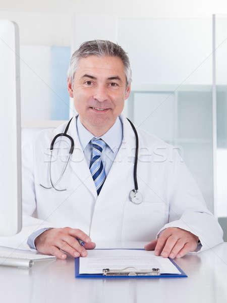 男医生侧脸照片_商业照片: 肖像 · 成熟 · 男医生 · 快乐 · 工作的 · 办公桌