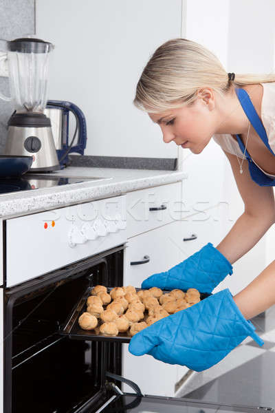 Woman Placing Cookies In Oven Stock photo © AndreyPopov
