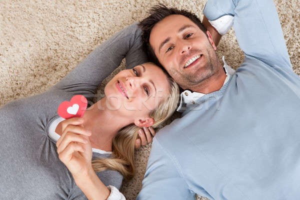 Man and woman lying head to head on the carpet Stock photo © AndreyPopov