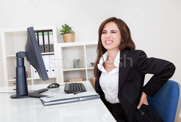 Businesswoman Having Backache At Work Stock photo © AndreyPopov