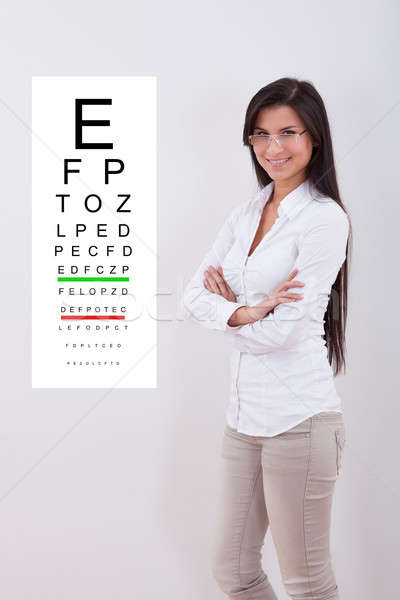 Woman pointing standing next to an eye chart Stock photo © AndreyPopov