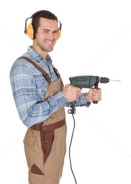 Worker holding drill and wearing hard hat Stock photo © AndreyPopov