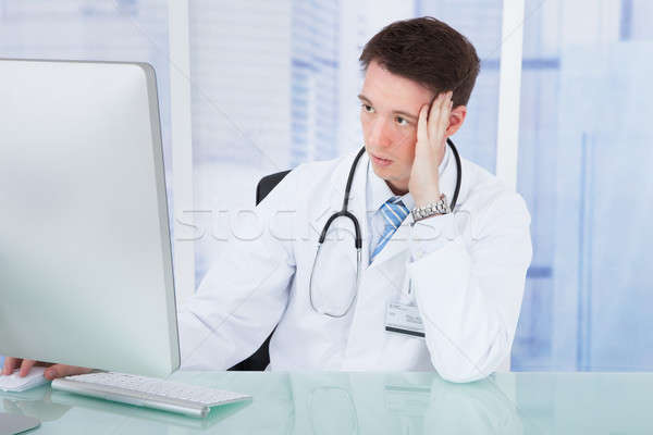 Worried Male Doctor Using Computer At Desk Stock photo © AndreyPopov