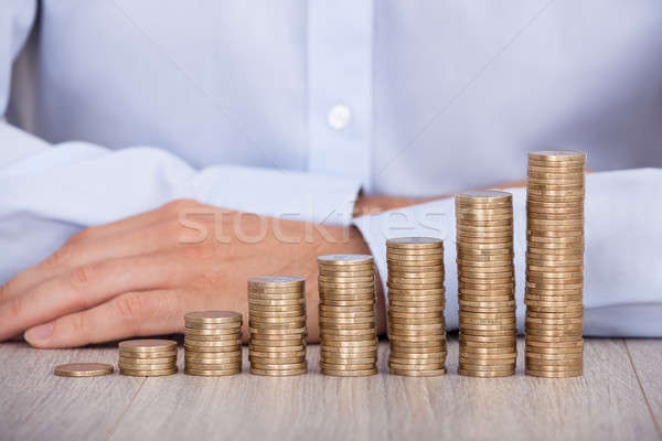 Businessman's Hand Behind Euro Coins At Desk Stock photo © AndreyPopov