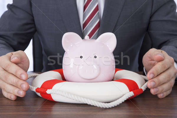 Businessman Sheltering Piggybank With Lifebelt At Desk Stock photo © AndreyPopov