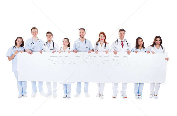 Large group of doctors and nurses with a banner Stock photo © AndreyPopov