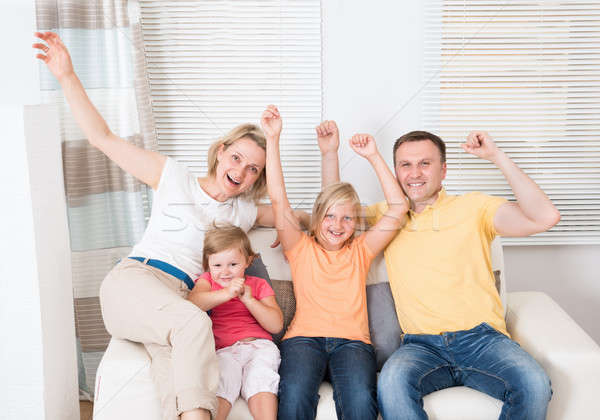 Cheering Family Sitting On Sofa Stock photo © AndreyPopov