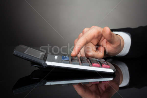 Stock photo: Businessman Using Calculator At Desk