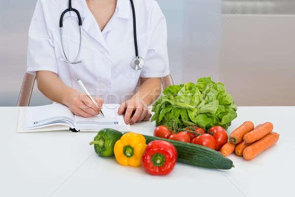 Female Dietician Writing Prescription Stock photo © AndreyPopov