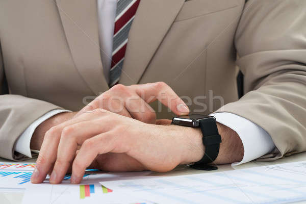 Businessman With Graph And Smartwatch Stock photo © AndreyPopov