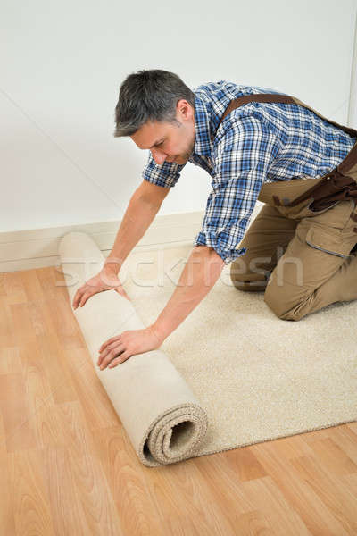 Worker Unrolling Carpet On Floor Stock photo © AndreyPopov