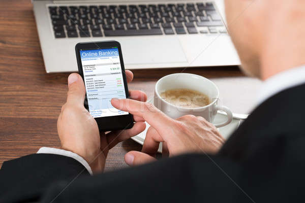Businessman Using Online Banking Service On Cellphone Stock photo © AndreyPopov