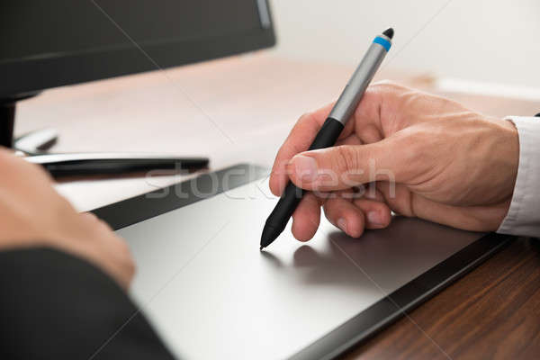 Businessman Drawing On Graphic Tablet Stock photo © AndreyPopov