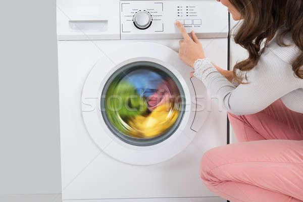Foto stock: Mulher · botão · máquina · de · lavar · roupa · mulher · jovem