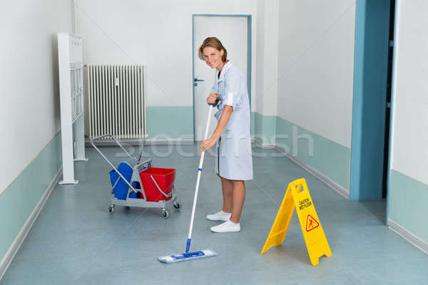 Janitor With Wet Caution Sign And Cleaning Equipments Stock photo © AndreyPopov
