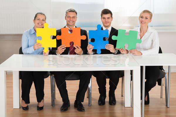 Businesspeople Holding Multi-colored Puzzles Stock photo © AndreyPopov
