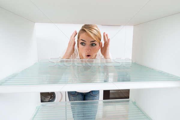 Shocked Woman Looking At Empty Refrigerator Stock photo © AndreyPopov