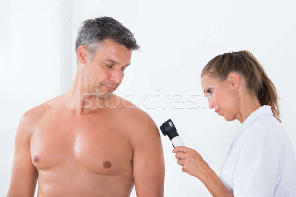 Doctor Examining Pigmented Skin Of Patient Stock photo © AndreyPopov