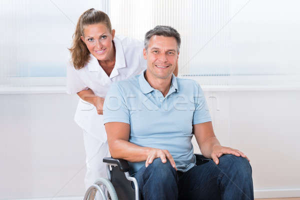 Doctor Carrying Patient On Wheelchair Stock photo © AndreyPopov