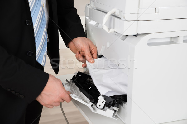 Businessman Removing Paper Stuck In Printer At Office Stock photo © AndreyPopov