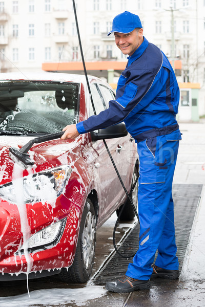 Confident Male Worker Washing Red Car At Garage Stock photo © AndreyPopov