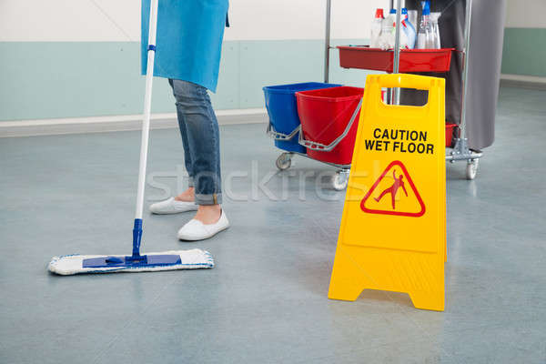 Female Janitor Mopping Corridor With Caution Sign Stock photo © AndreyPopov