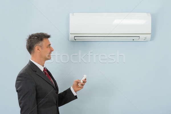 Empresario control remoto acondicionador de aire oficina maduro Foto stock © AndreyPopov