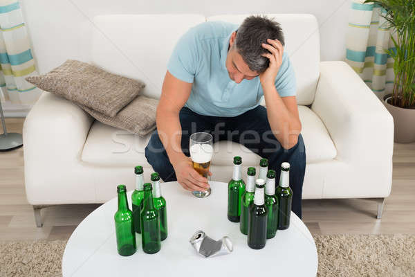 Man Sitting On Sofa In Front Of Beer Stock photo © AndreyPopov