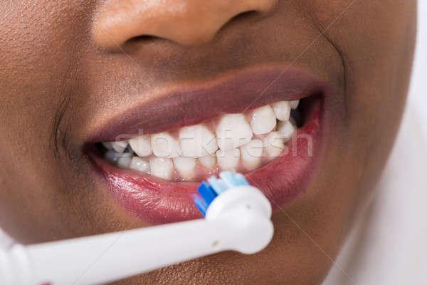 Nő fogmosás elektromos fogkefe közelkép otthon Stock fotó © AndreyPopov