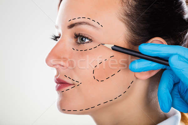 Surgeon Drawing Correction Lines On Young Woman Face Stock photo © AndreyPopov