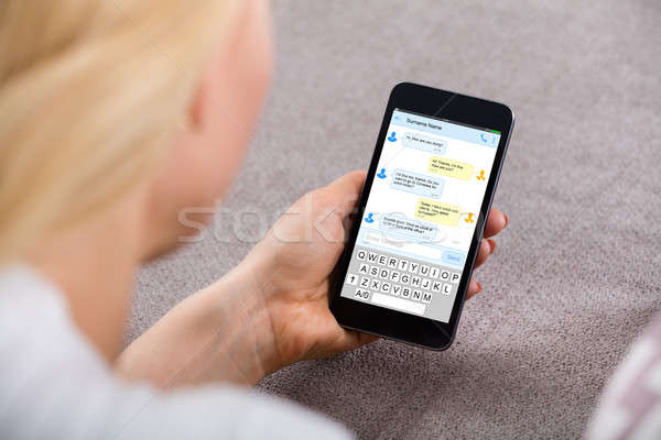 Woman Sending Text Message Using Mobile Phone Stock photo © AndreyPopov