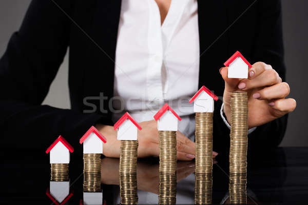 Businesswoman Arranging House Model On Stacked Coins Stock photo © AndreyPopov