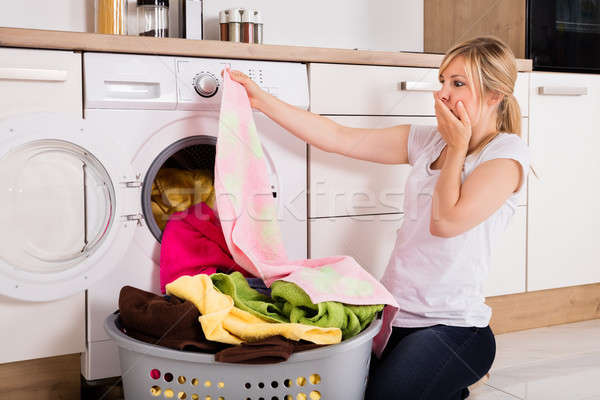 Woman Looking At Cloth Near Washing Machine Stock photo © AndreyPopov