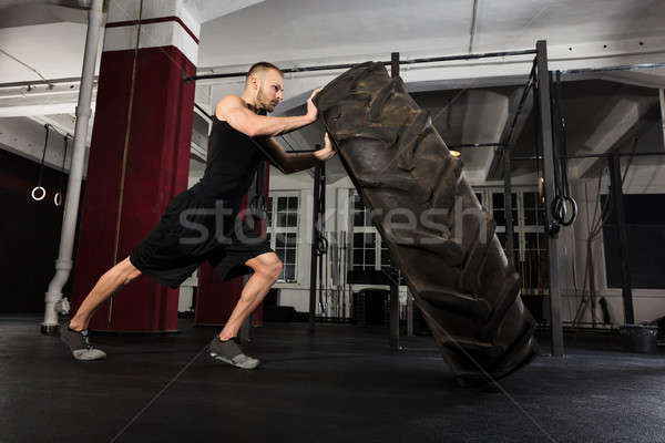 Young Man Pushing Tire Stock photo © AndreyPopov