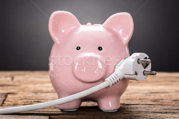 Piggybank With Plug On Wooden Table Stock photo © AndreyPopov